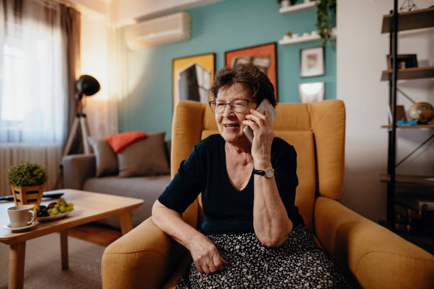 Portrait of senior woman at home using mobile phone and technologies stock photo