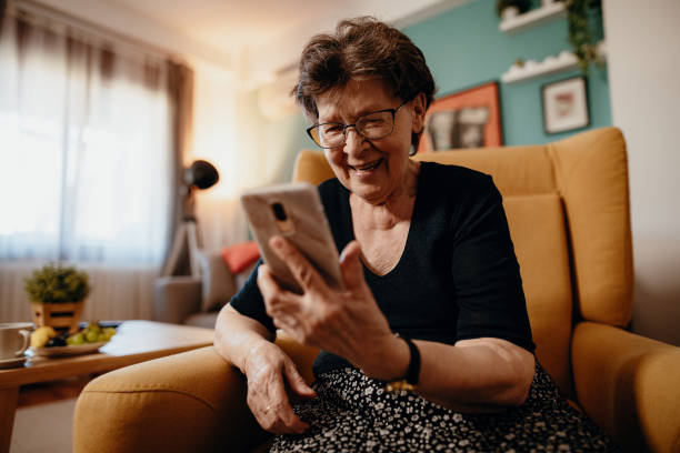 Portrait of senior woman at home using mobile phone and technologies Video portrait of senior 78 year old woman at home eastern european descent stock pictures, royalty-free photos & images