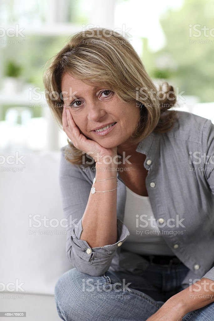 Portrait of senior woman at home with hand under chin royalty-free stock photo
