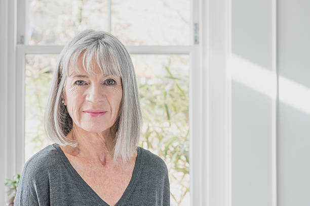 portrait of senior woman by window with grey bob - vrouw 60 stockfoto's en -beelden