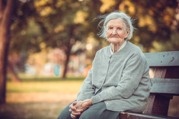 Portrait of senior woman in autumn park stock photo