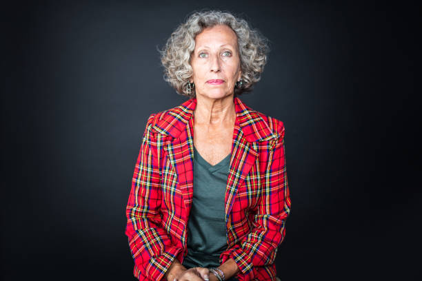 Portrait of senior woman in red plaid shirt Portrait of confident senior woman with curly gray hair. Female is sitting against black background. She is in unbuttoned red plaid shirt. 60 64 years stock pictures, royalty-free photos & images