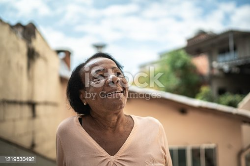 500841556 istock photo Portrait of senior woman looking up dreaming at house 1219530492