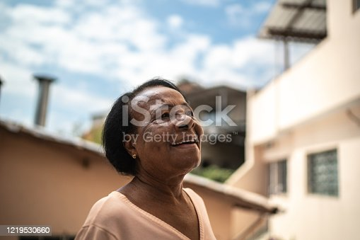 500841556 istock photo Portrait of senior woman looking up dreaming at house 1219530660