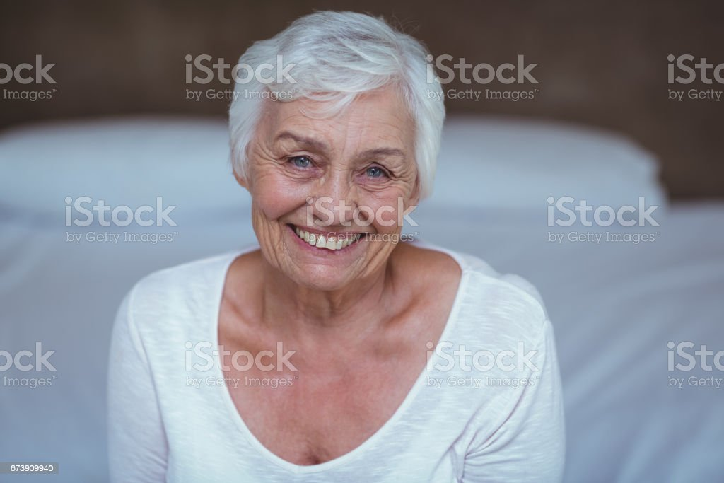 Portrait d'une femme senior sur lit photo libre de droits
