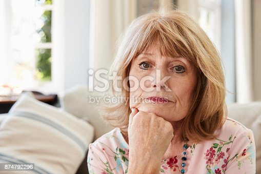 874789168istockphoto Portrait Of Senior Woman On Sofa Suffering From Depression 874792296