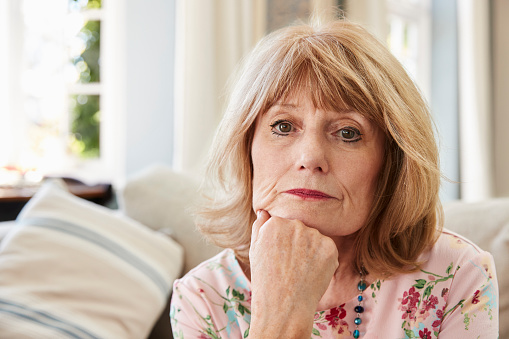 874789168 istock photo Portrait Of Senior Woman On Sofa Suffering From Depression 874792296