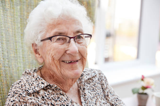 Portrait Of Senior Woman Sitting In Chair In Lounge Of Retirement Home stock photo