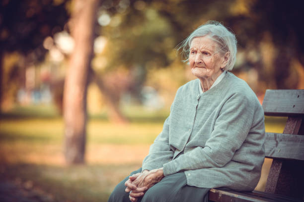 Portrait of senior woman sitting on bench in autumn park. Old lady feeling lonely and sad. stock photo