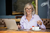 Portrait of senior woman using laptop computer while eating breakfast