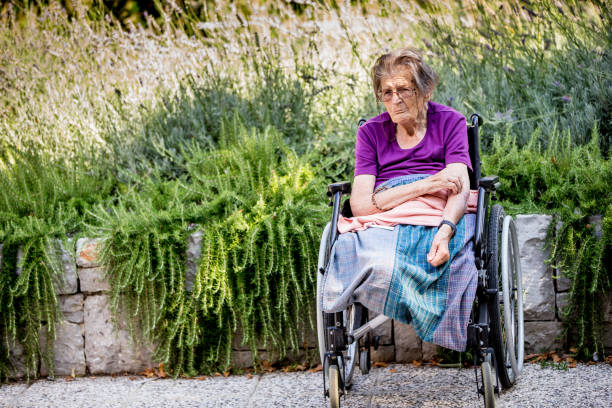 Portrait Of Senior Woman With Amputeted Legs Sitting Outdoors On Wheelchair stock photo
