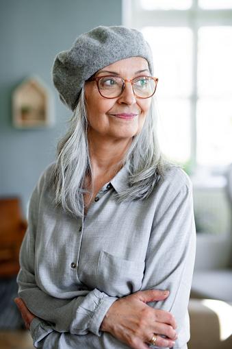 Studio portrait of senior woman with gray beret standing indoors against dark background.