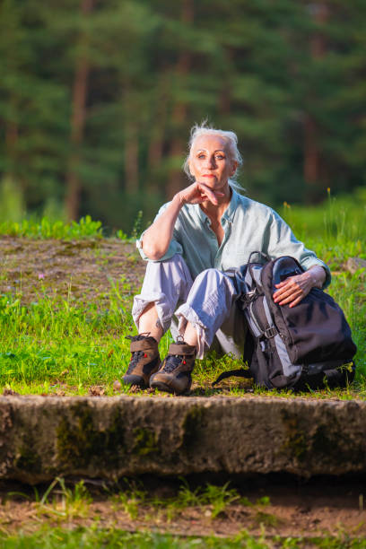 Portrait of Senior Woman With Tourist Backpack Dreaming in Forest Outdoors On Nature Background.Vertical Image
