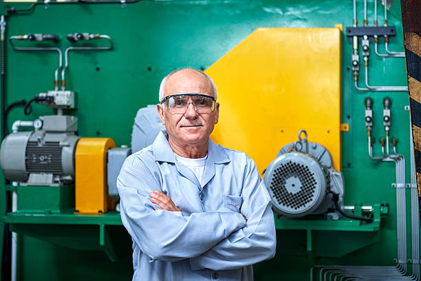 portrait of senior worker in factory - manufacturing occupation stock photos and pictures