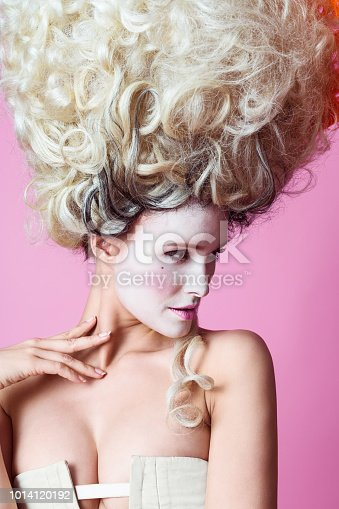 Portrait of beautiful woman wearing a big wig in baroque style. Standing against pink background.