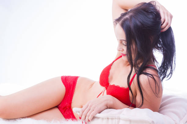 Portrait of Sensual Mature Caucasian Brunette Female in Red Lingerie. Touching Hair and Posing Against White background. Horizontal Image