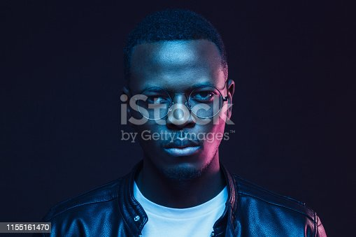 Portrait of serious African man wearing glasses and leather jacket at night