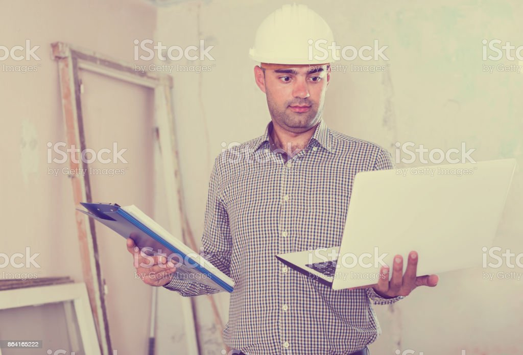 Portrait of serious architect working at the notebook in helmet with documents royalty-free stock photo