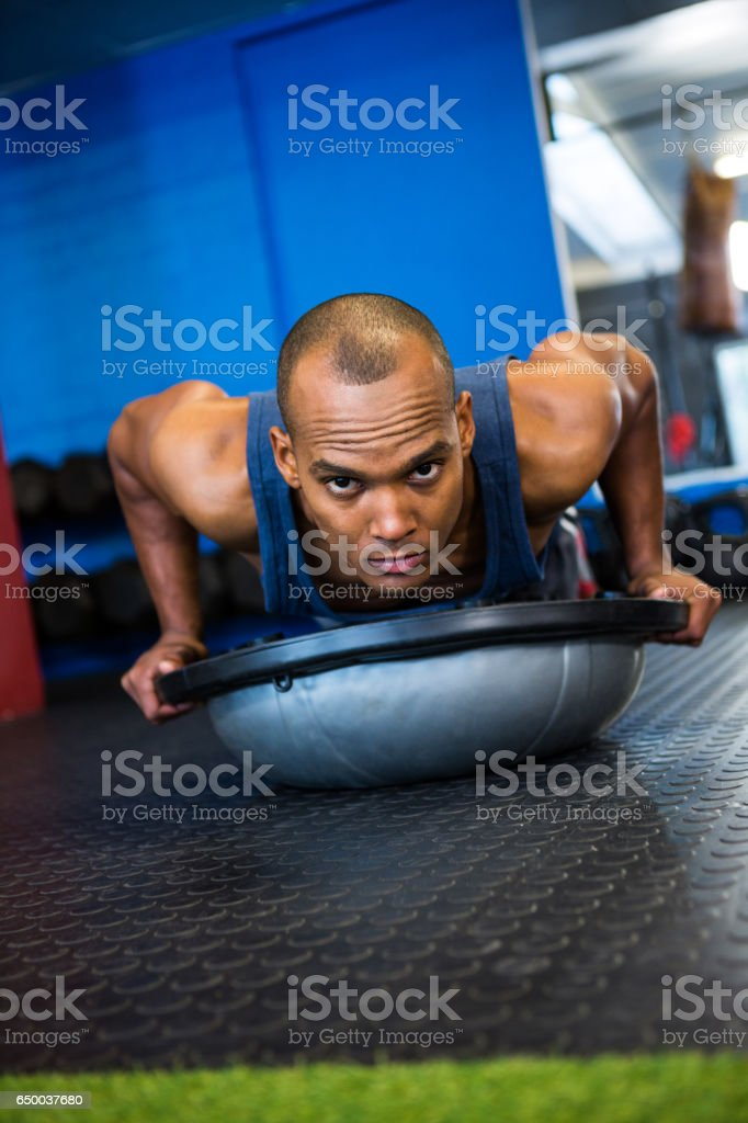 Portrait of serious athlete with BOSU ball in gym stock photo