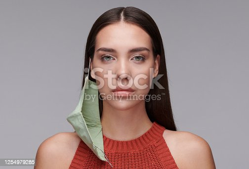 Brunette woman with mask hanging on ear