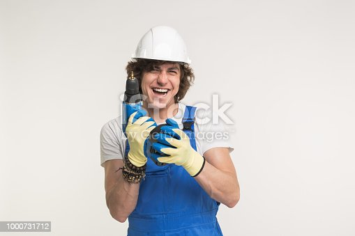 istock Portrait of serious builder men in white helmet with screwdriver wearing gloves and blue overalls 1000731712