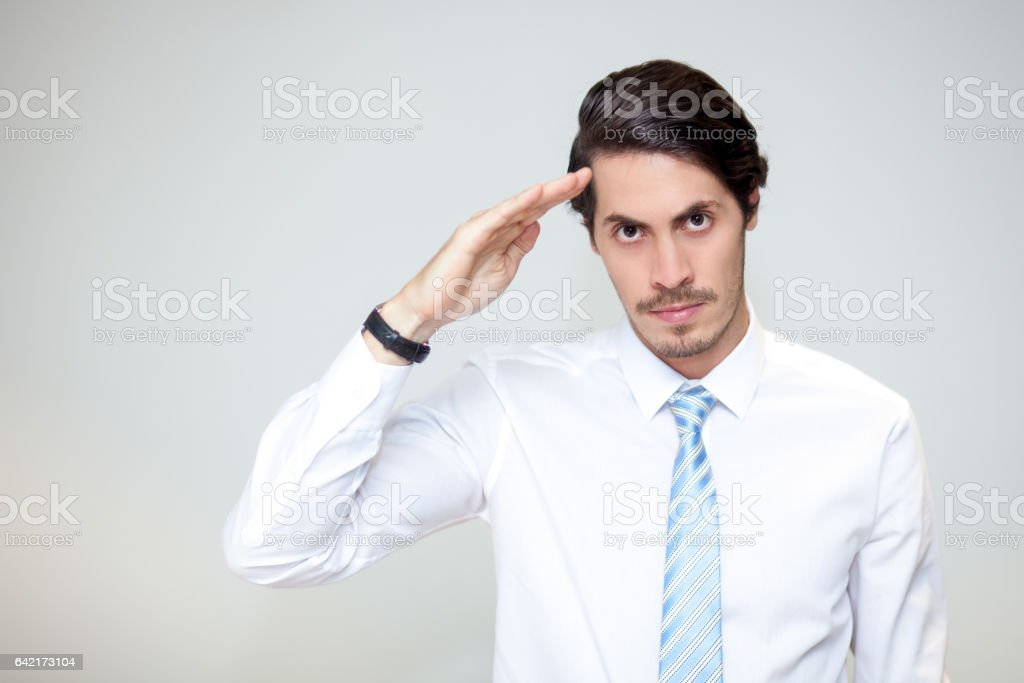 Portrait of serious businessman saluting at camera stock photo
