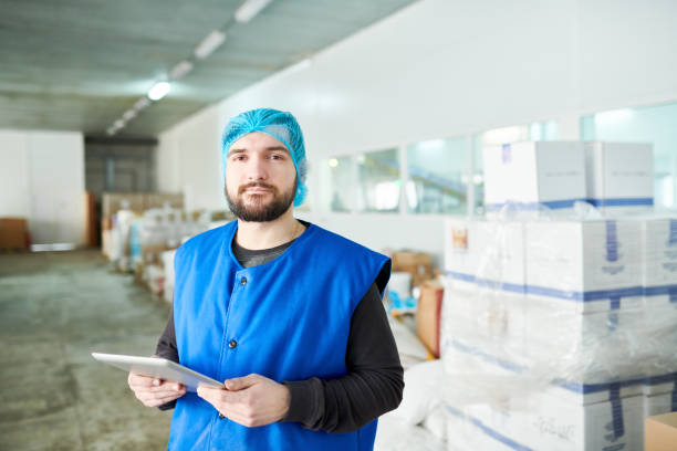 Portrait of serious confident handsome bearded warehouse worker in vest and sterile cap using tablet in storage room with stacks if boxes Warehouse specialist analyzing products with tablet food warehouse stock pictures, royalty-free photos & images