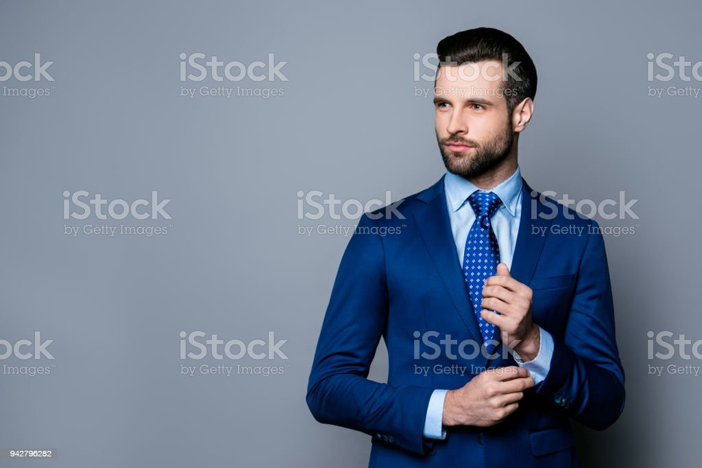 Portrait of serious fashionable handsome man in blue suit and tie  buttoning cufflinks stock photo