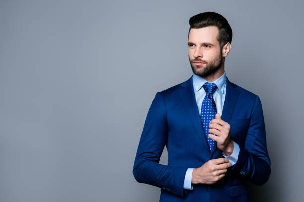 portrait de grave à la mode bel homme en costume bleu et cravate, boutons de manchettes de boutonnage - cravate photos et images de collection