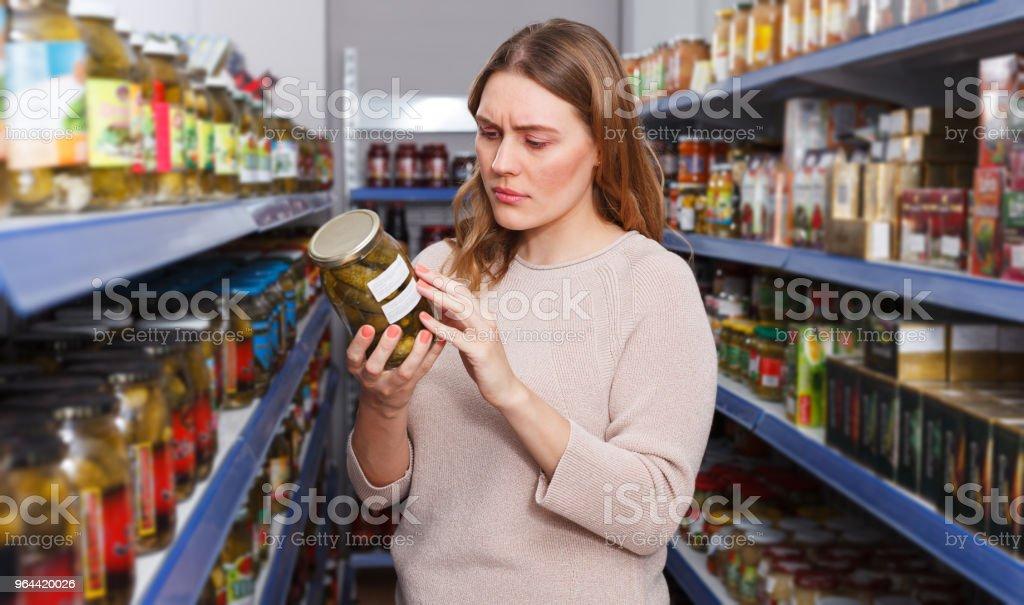 Portret van ernstige vrouwelijke kiezen augurk goederen in voedsel winkel - Royalty-free 30-39 jaar Stockfoto