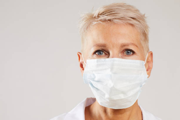 Portrait of serious female doctor with short blond hair wearing surgical mask standing against white background stock photo