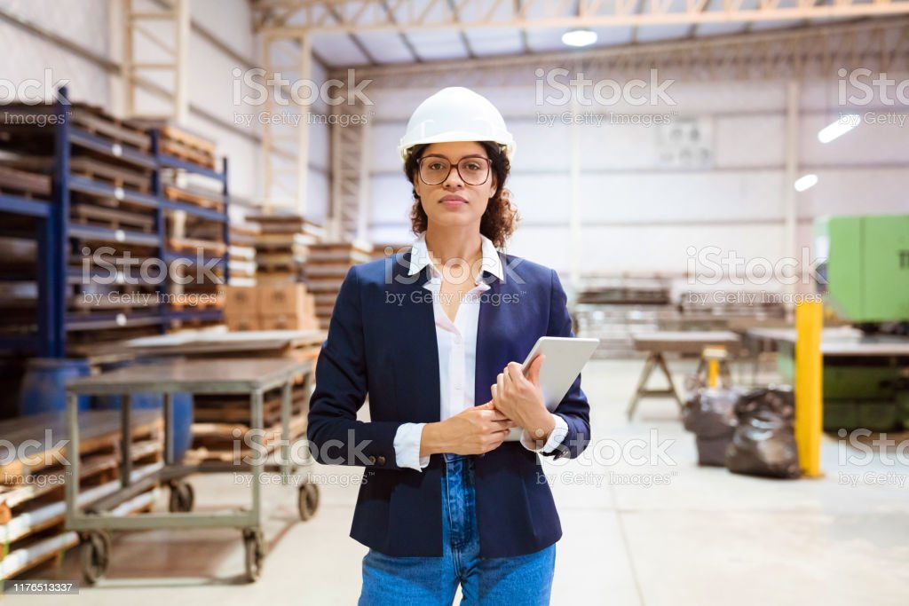 Portrait of serious female manager in factory Portrait of serious female manager standing in factory. Expertise is wearing hardhat while holding digital tablet. She is with confident look on her face. 30-34 Years Stock Photo