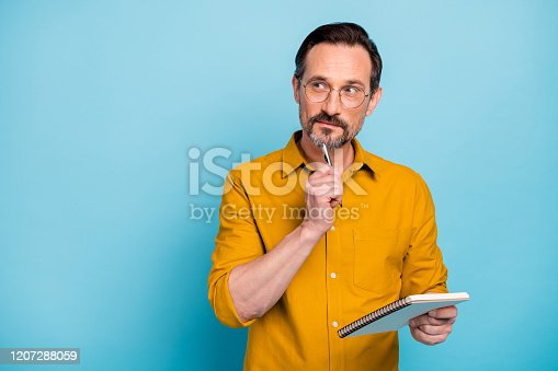 Portrait of serious focused man write essay in his copy book think thoughts, contemplate wear modern clothes isolated over blue color background