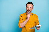 istock Portrait of serious focused man write essay in his copy book think thoughts contemplate wear modern clothes isolated over blue color background 1207288059