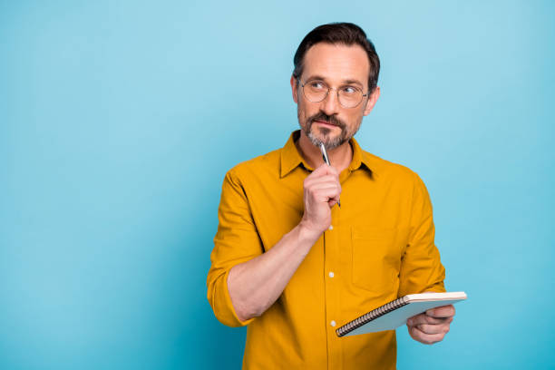 Portrait of serious focused man write essay in his copy book think thoughts contemplate wear modern clothes isolated over blue color background stock photo