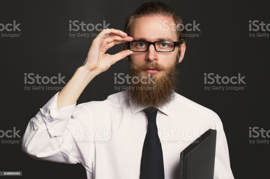 Portrait of serious hipster bearded businessman with documents. Boss in glasses posing in business suit on black background. stock photo