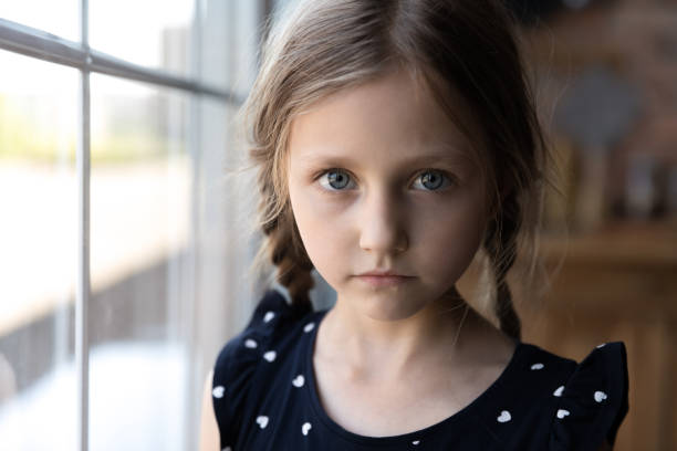 Portrait of serious little school age girl standing by window stock photo