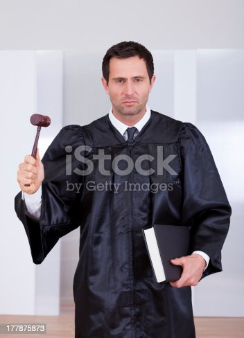 Portrait Of A Serious Male Judge Holding The Gavel And Book