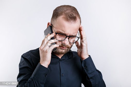865714662istockphoto Portrait of serious male wears glasses and black shirt, has phone conversation 1142418667