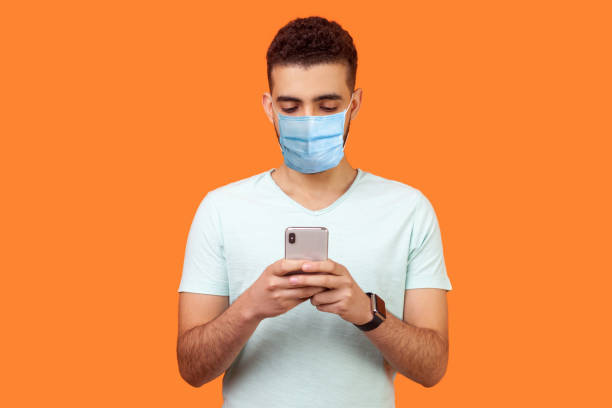 Portrait of serious man with medical mask in casual white t-shirt using cellphone, texting chatting in social media or surfing mobile web. stock photo