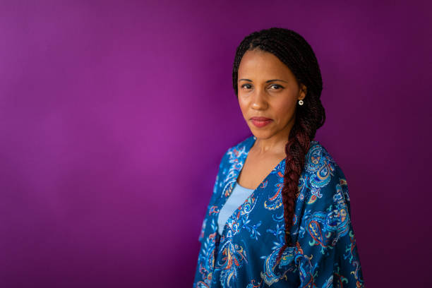 Portrait of serious mixed race woman in front of purple wall stock photo