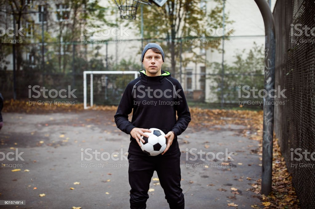 Portrait of serious player holding soccer ball royalty-free stock photo