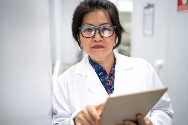 Portrait of serious scientist holding digital tablet Portrait of serious scientist holding digital tablet microbiologist stock pictures, royalty-free photos & images
