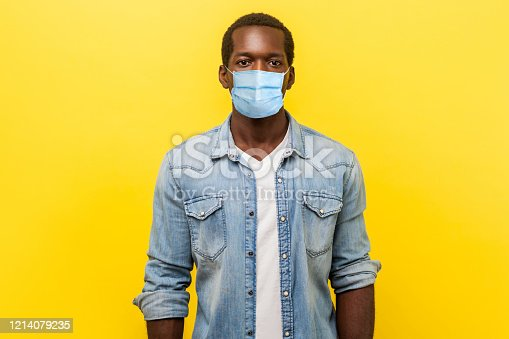 Portrait of serious self-assertive handsome man with medical mask with rolled up sleeves looking smart and professional, freelancer or employee. indoor studio shot isolated on yellow background