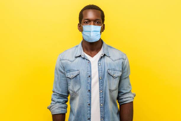 retrato de um homem bonito auto-assertivo com máscara médica com mangas arregaçadas parecendo inteligente e profissional, freelancer ou empregado. - lifestyle color background - fotografias e filmes do acervo