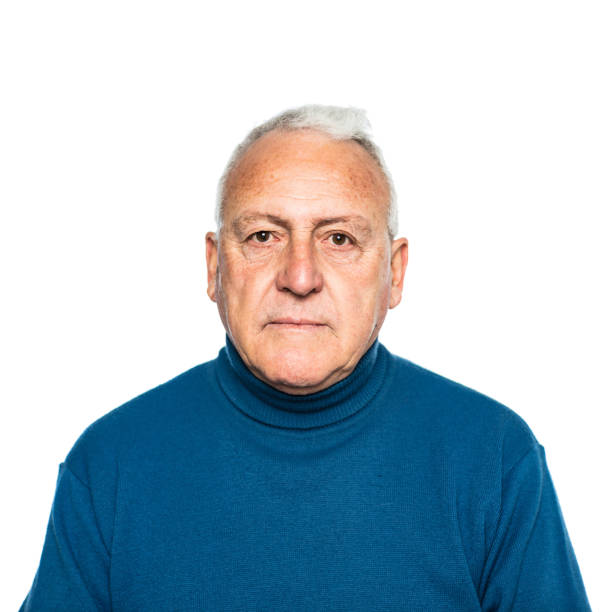 Portrait of serious senior man in sweater Portrait of serious senior man. Elderly male is against white background. He is wearing blue turtleneck sweater. 60 64 years stock pictures, royalty-free photos & images