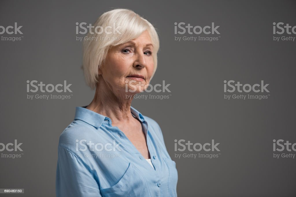 portrait of serious senior woman isolated on grey in studio - Photo