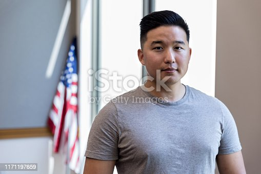 Portrait of serious veteran with American flag in background