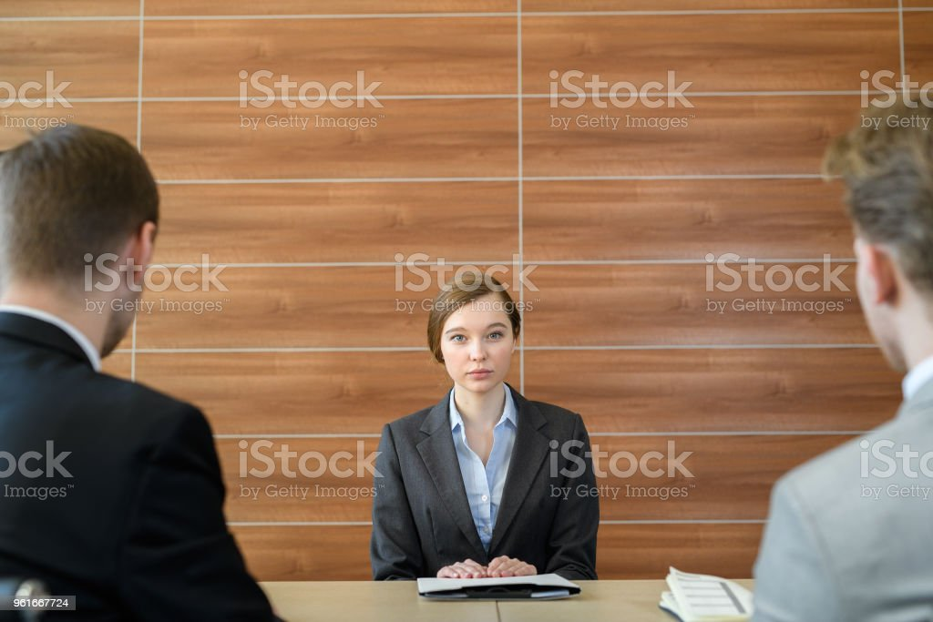 Portrait of serious worried young female job candidate sitting at table with employers and listening to their questions at job interview stock photo