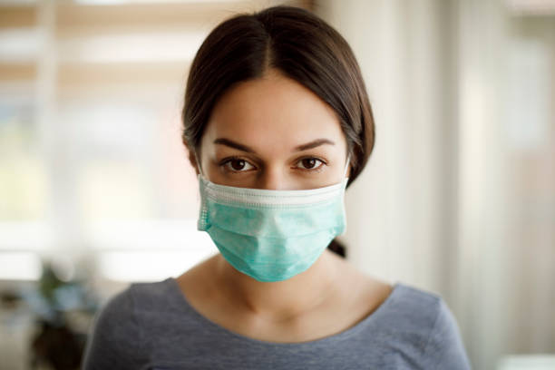 Portrait of serious young woman with face protective mask at home stock photo